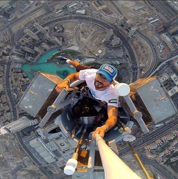 мужчина делает селфи на вершине небоскреба