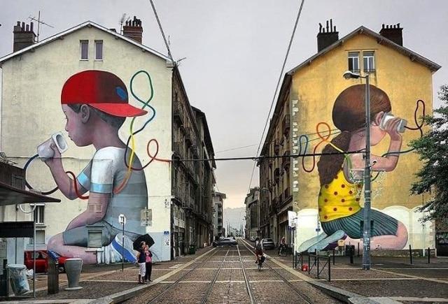 Мальчик на оном здании и девочка на другом общаются по проводу