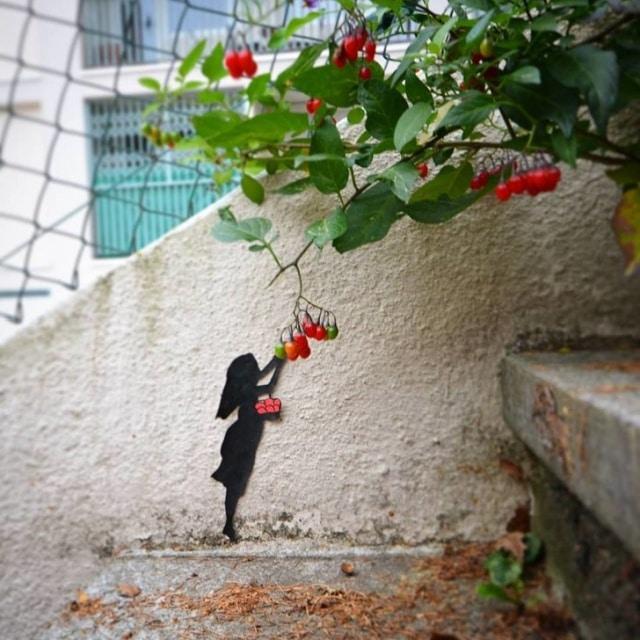 Нарисованная девушка срывает настоящие ягоды