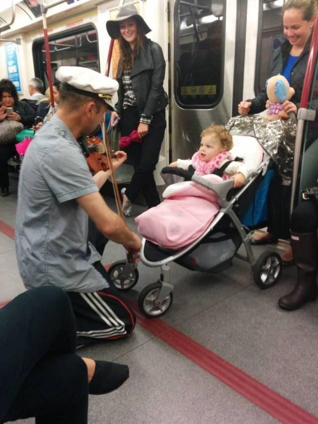 мужчина в метро играет для девочки
