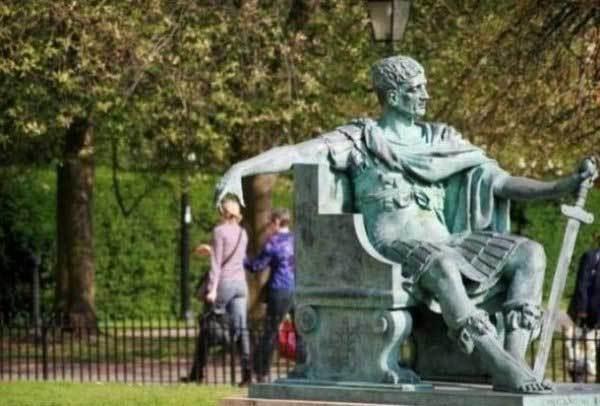 памятник держит девушку за голову