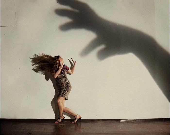 девушка убегает от тени руки на стене