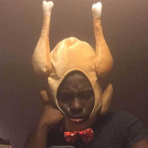 чернокожий парень в шапке в виде курицы