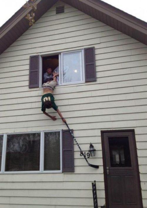 мужчина висит с клюшкой из окна