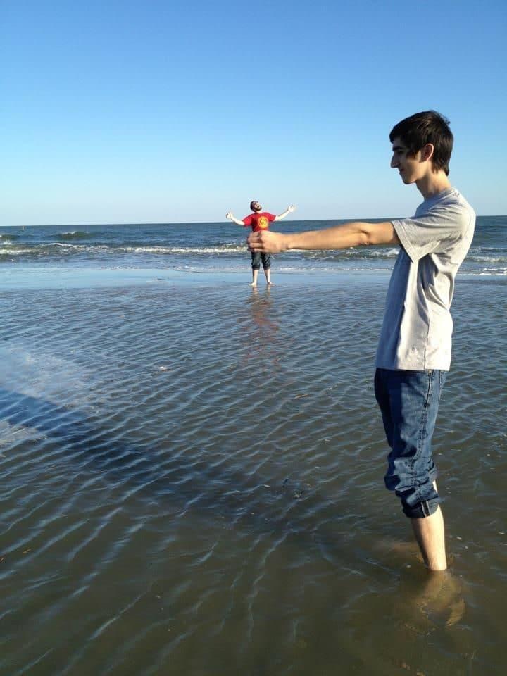 парень держит друга в руке над морем