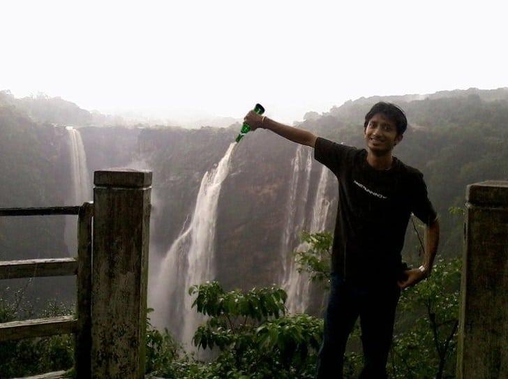 мужчина с бутылкой и водопад