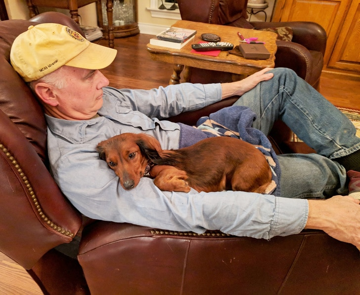 мужчина в кепке сидит с собакой в кресле