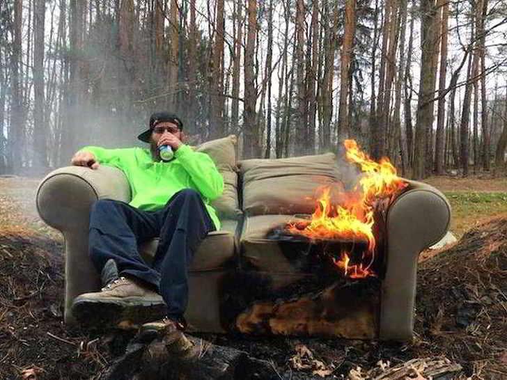парень сидит на горящем диване