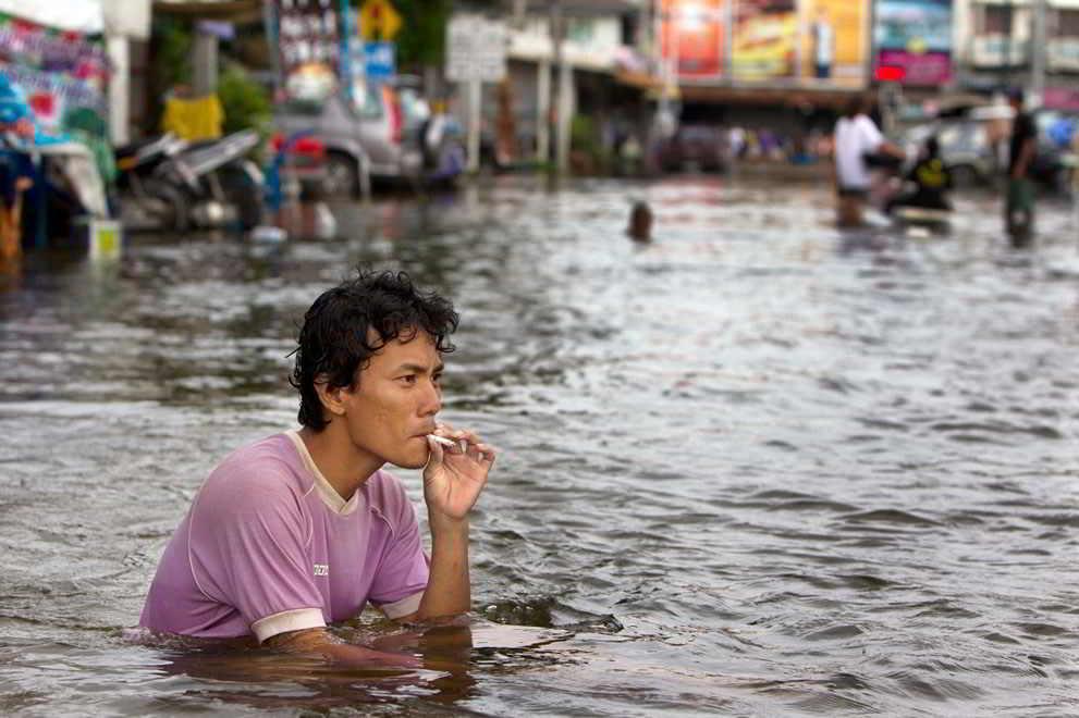 парень курит, сидя в воде
