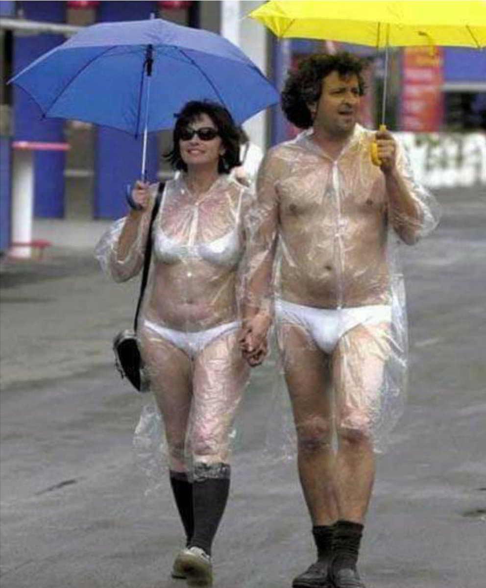 пара под зонтами в прозрачных дождевиках
