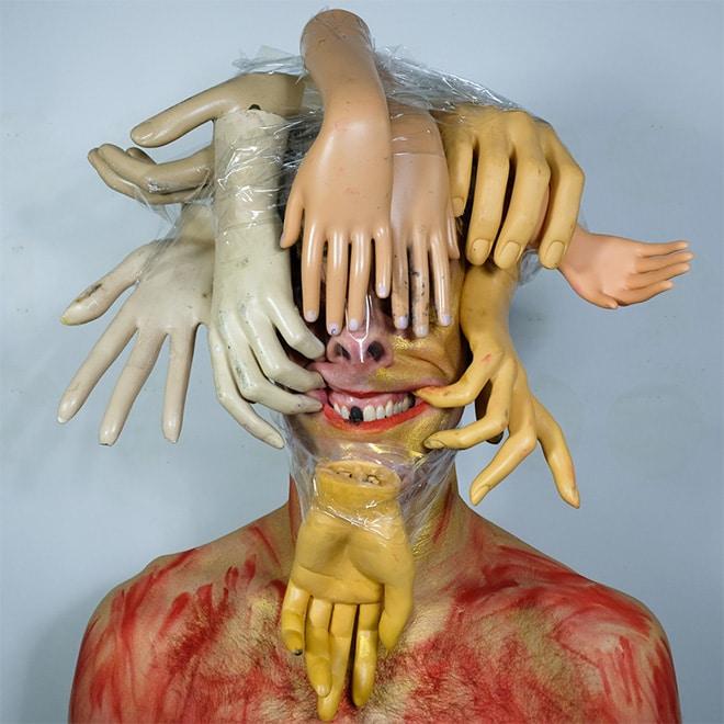 мужчина с игрушечными руками на голове