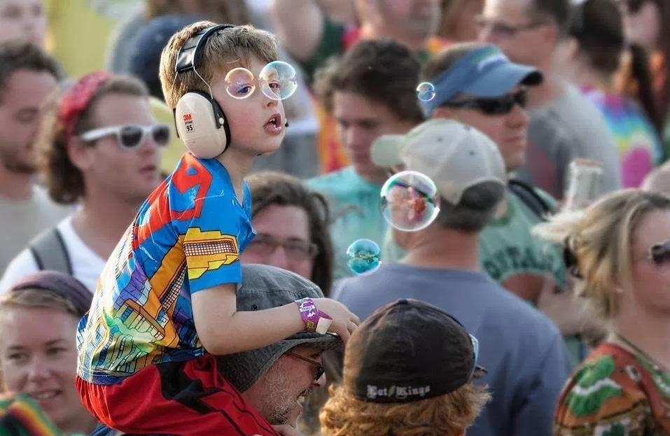 мальчик на плечах у мужчины в толпе