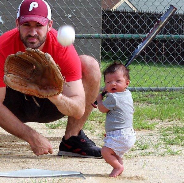 папа играет с дочерью в бейсбол