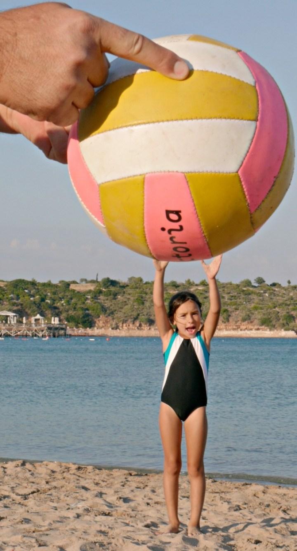 девочка держит мяч над головой