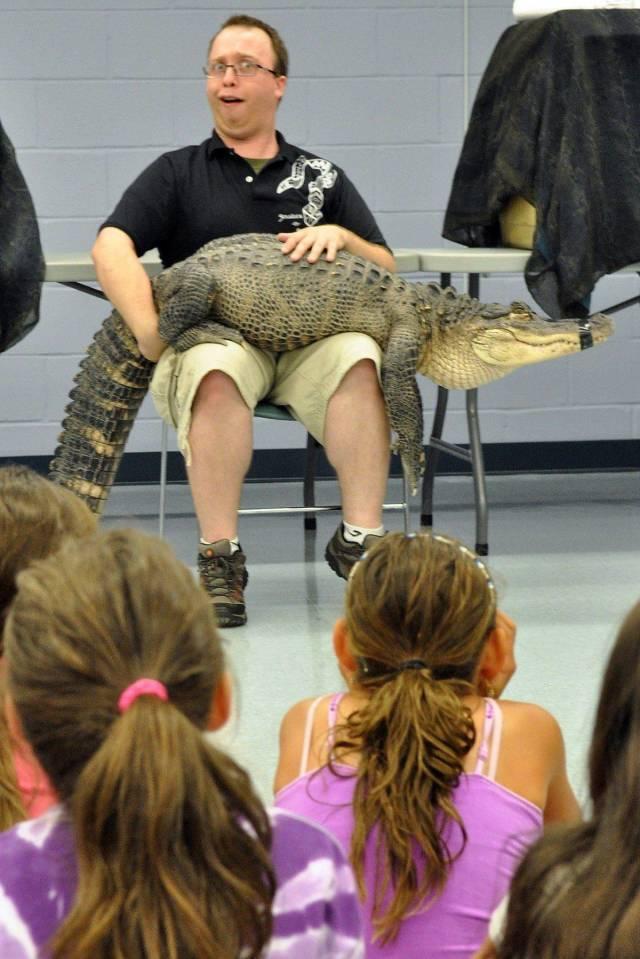 мужчина с крокодилом на коленях