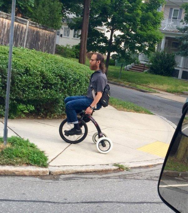 бородатый мужчина на трехколесном велосипеде