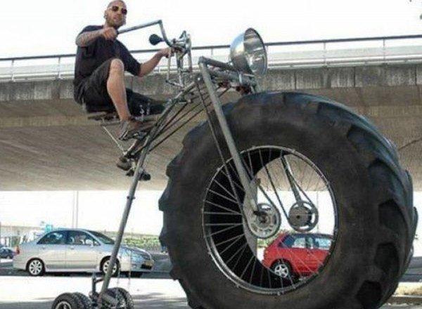парень на велосипеде с колесом от трактора