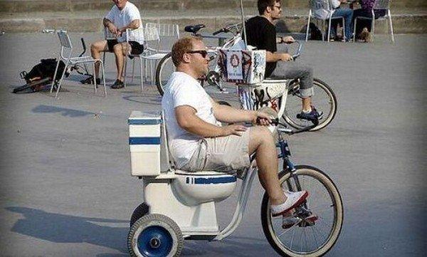 мужчина на велосипеде с унитазом