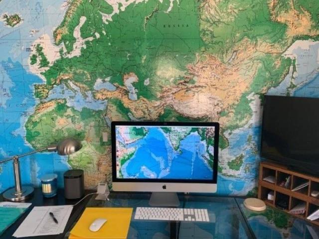 карта мира на стене и компьютер