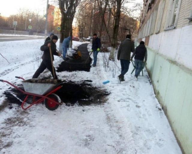 люди кладут асфальт на снег
