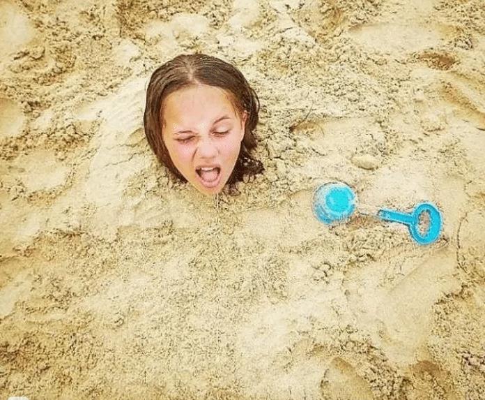 девушка закопана в песке
