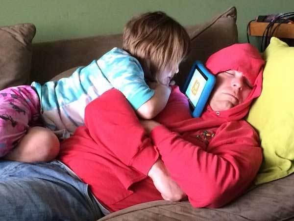 девочка смотрит планшет верхом на спящем папе