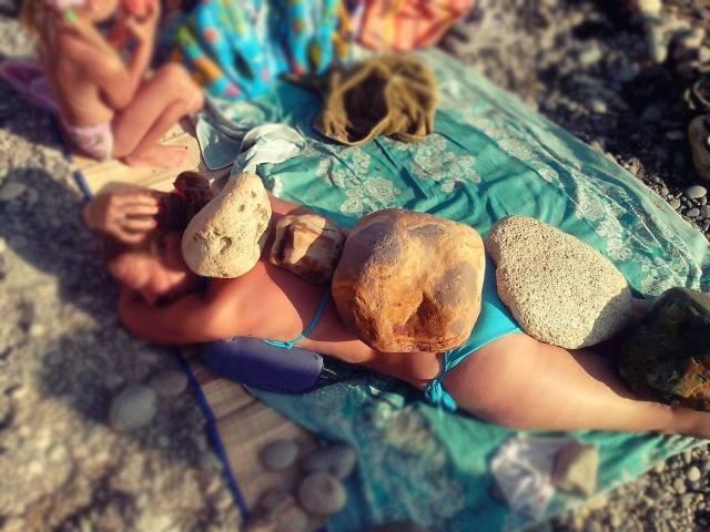 женщина на пляже с камнями на спине