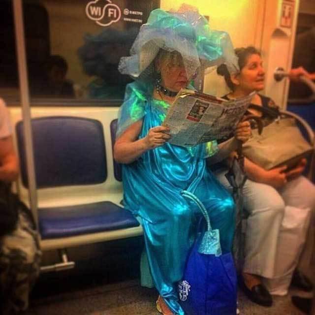женщина читает газету в метро