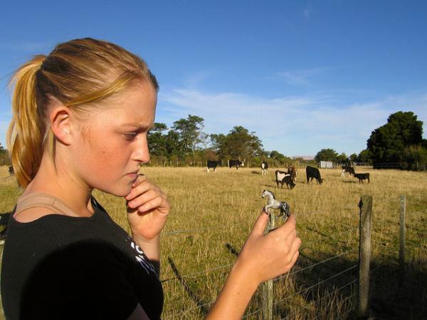 девушка с игрушечной лошадкой в руке