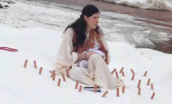 девушка сидит на снегу с сосисками на шее