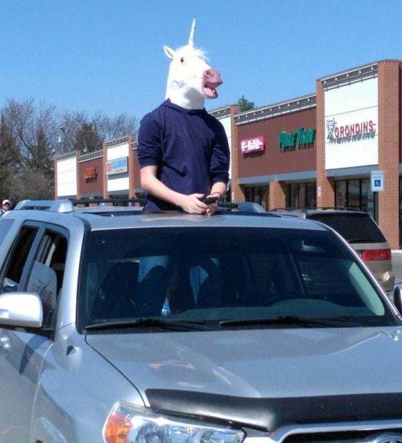 парень с маске единорога в машине