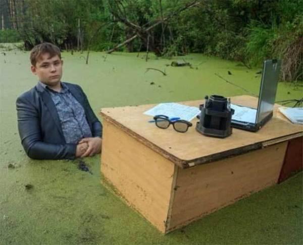 парень сидит за столом в болоте
