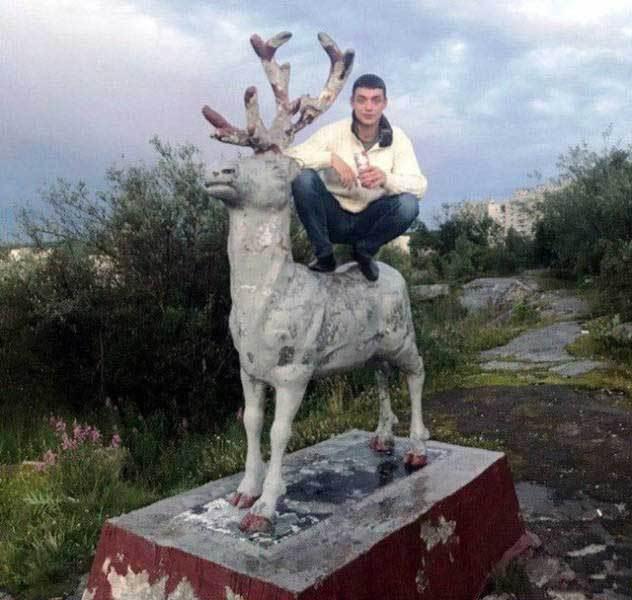 парень сидит на памятнике оленю