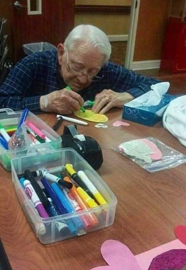 мужчина рисует валентинку жене