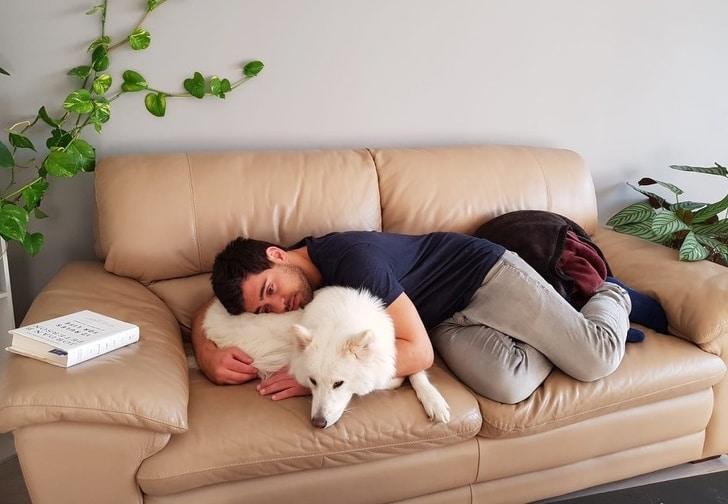 парень лежит в обнимку с собакой на диване