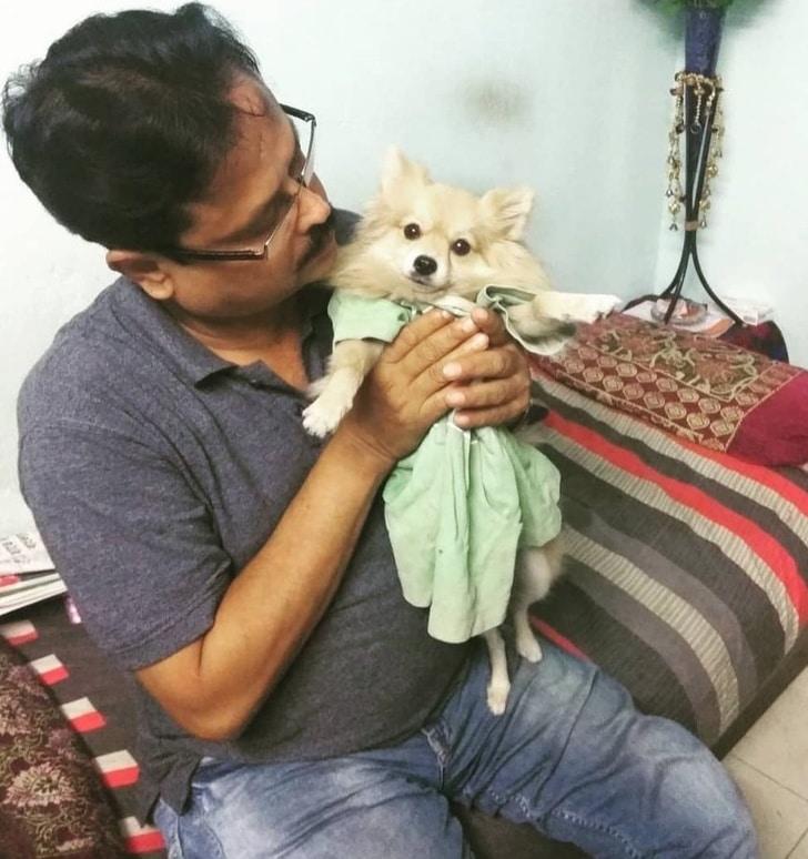 мужчина держит собаку в платье