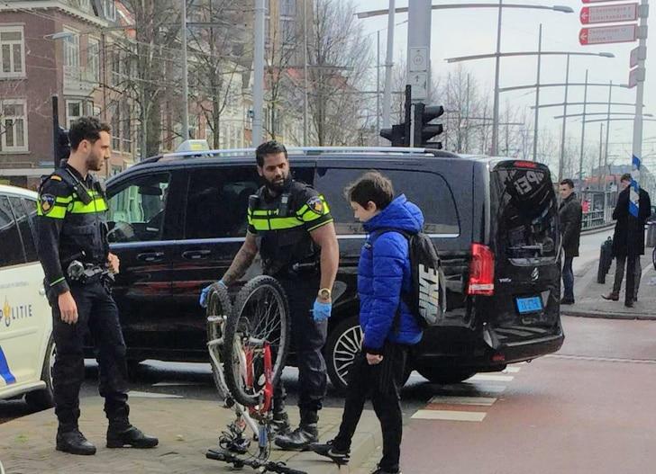 полицейские и мальчик с велосипедом