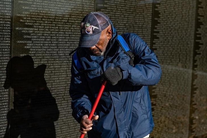 мужчина метет тропу возле памятника