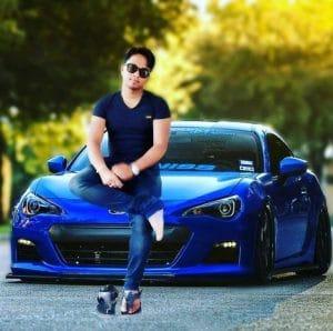 парень сидит на синей машине