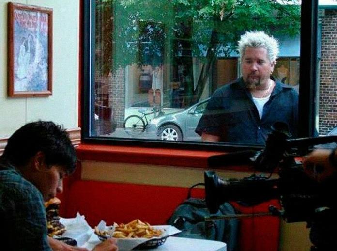 мужчина смотрит через окно на картошку фри
