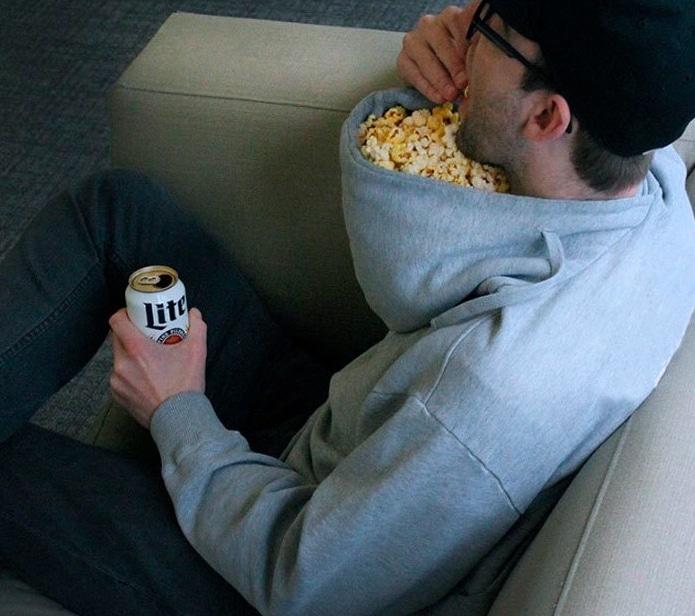 парень ест попкорн из капюшона