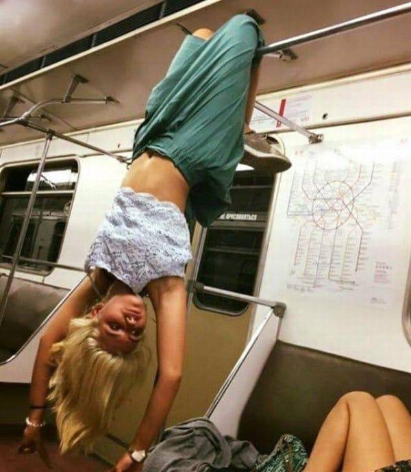 блондинка висит вниз ногами в вагоне метро