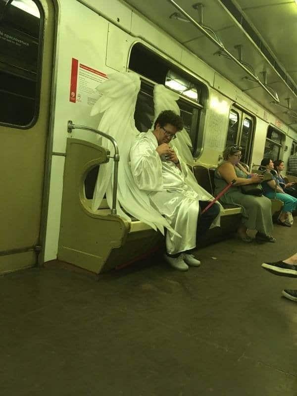 женщина в костюме ангела в метро