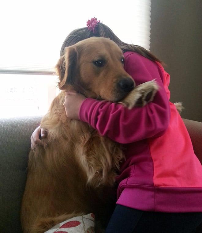 пес обнимается с девочкой