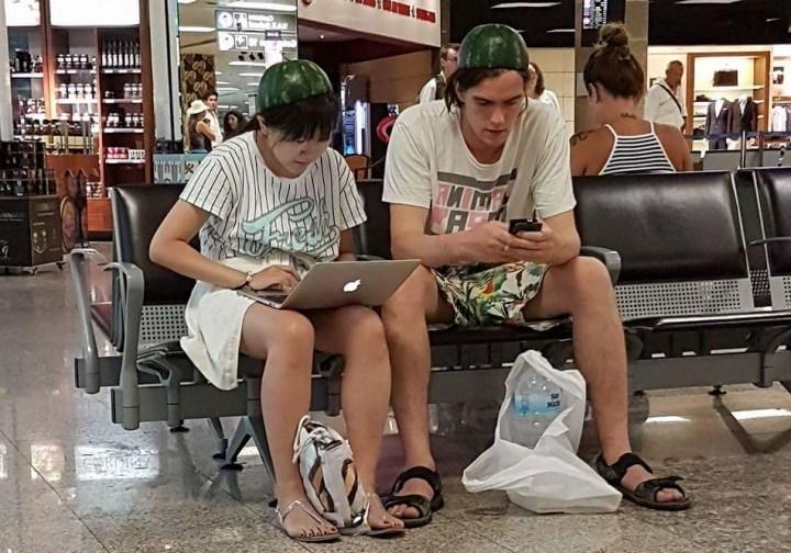 молодежь с ноутбуком и телефоном в аэропорту