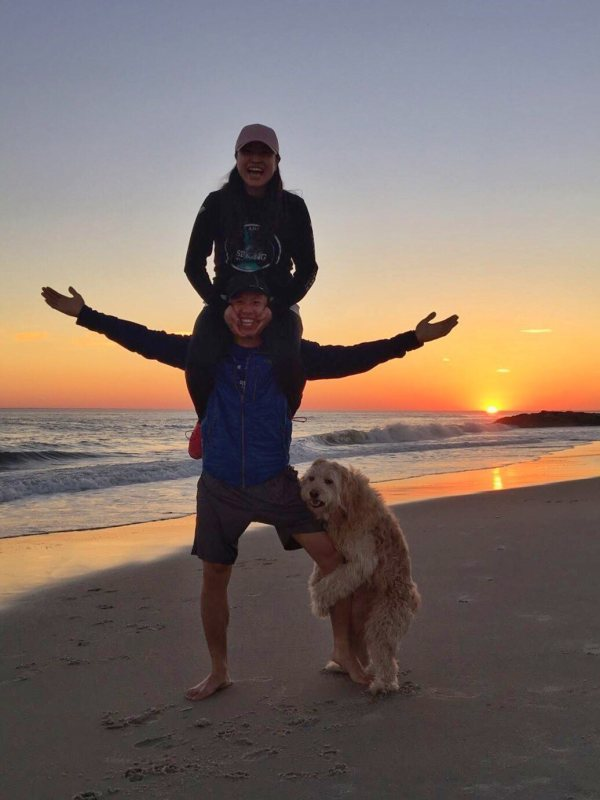пара с собакой у моря на закате