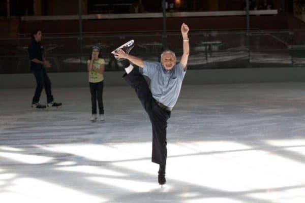 старик показывает шпагат на коньках