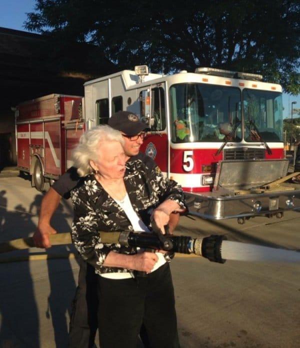 старушка держит брандспойт