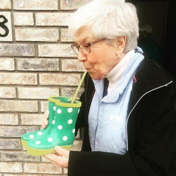 старушка пьет из сапога