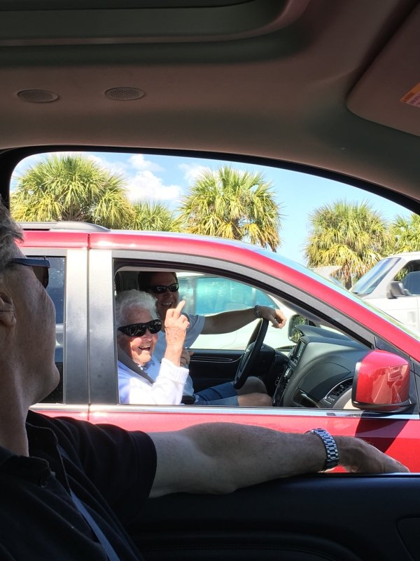 старушка показывает средний палец из машины